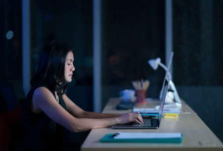 Pretty business woman working alone in dark office, workhard she close eye