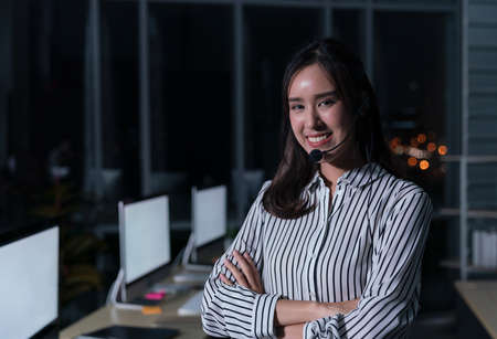 Thai portrait of business person wearing headset working, Young friendly operator woman agent in a call centre. 免版税图像