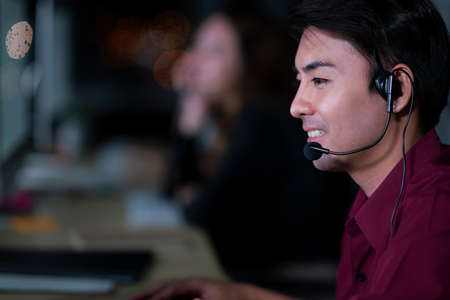 Thai Asian man customer services care operators working night shift in call center for helping assistance client in workplace at night time, Friendly helpdesk operator working at night