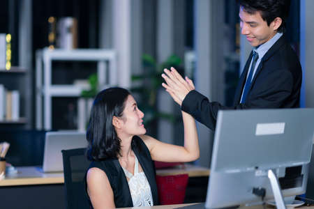 Business man and business woman hold hand together in office night, business team touching hands together after complete a deal in meeting