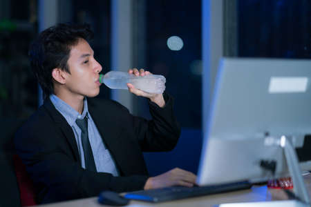Young asian handsome business man drinking water after work hard in office at night, businessmen relax after working, business success concept