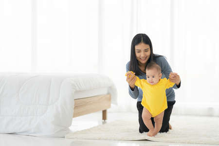 My little girl takes first steps. family happy little baby learning to walk with mother help at home 免版税图像