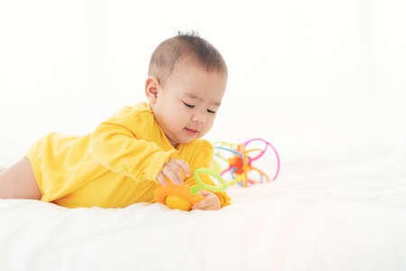 Cute thai newborn baby playing  funny in bed. Small baby in diaper lying on his belly on white bed with toys