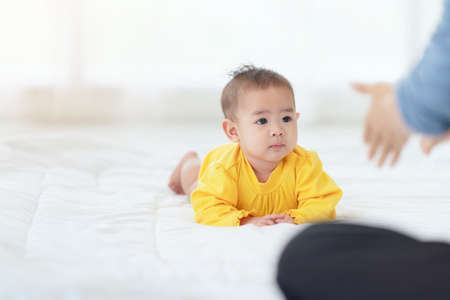 Happy baby go on caepet at home. child and parenthood concept, mother playing with little baby at home 免版税图像