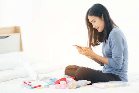 Single mom start working day on a laptop sitting on the bed in the morning. Working from home concept,  shopping online