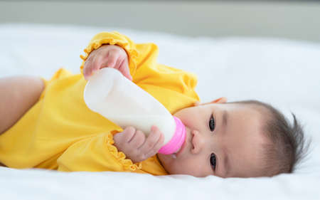 Cute baby with bottle on bed, Thai little Asian child lying on white bed drinking milk from bottle