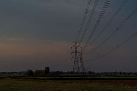 high voltage power lines in a field against a sunset