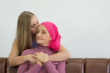 Young adult female cancer patient spending time with her daughter at home. Take medicine family support concept.