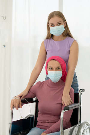 Young daughter embracing her sick mom who wearing headscarf on wheelchair, giving support battling through cancer. 免版税图像