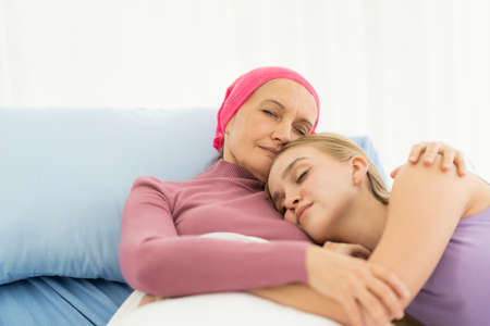 Young adult female cancer patient spending time with hug her daughter on bed at hospital. family support concept.