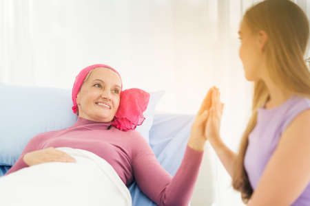 Cancer woman lying supported by mum at home. trust and ethics concept
