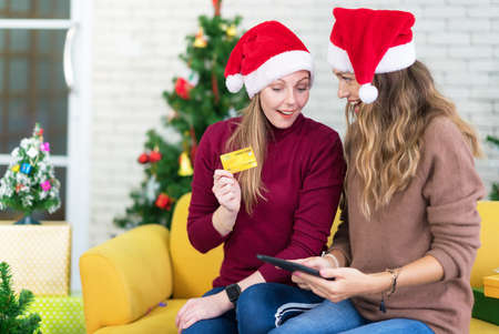 portrait of woman and friend showing a blank credit card in christmas holidays, Christmas and New Year shopping on the Internet, payment by credit card.
