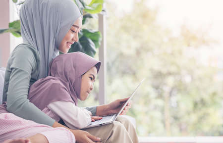 Asian muslim mother and daughter smiling when using laptop together, browsing internet or watching streaming movie
