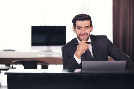 Portrait of happy businessman sitting at office desk