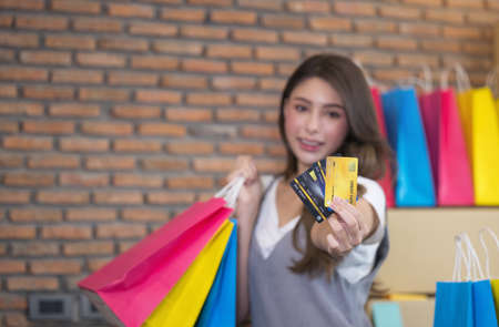 Young asian woman smile with success SME business  and shopping bag in hand for online shopping at home.