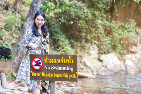 Thai women point to forbidden to swim sign in this area contradiction