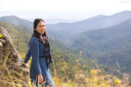 Asian attractive young woman traveler tourist standing  looking at mountain valley nature landscape summer scenery feeling peaceful joyful happy success