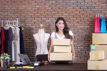 beautiful Asian woman standing among several boxes and checking parcels, working in the house office. Concept for home base business and startup ownership 写真素材