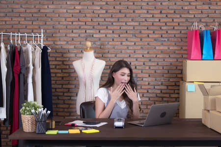 Young business woman working selling online. Surprise and shock face of asian woman success on making big sale of his online store. Online shopping 写真素材