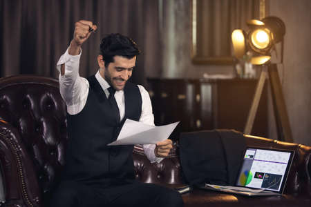Young man celebrating in office, Businessman cheering at his desk