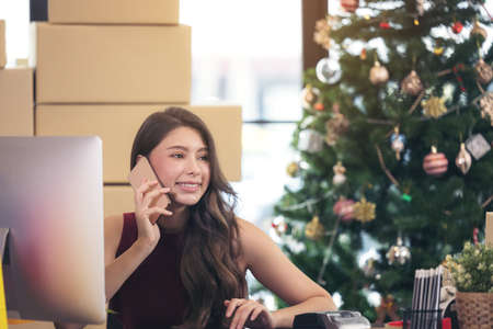 smiling young woman working from home and talking on smartphone 写真素材