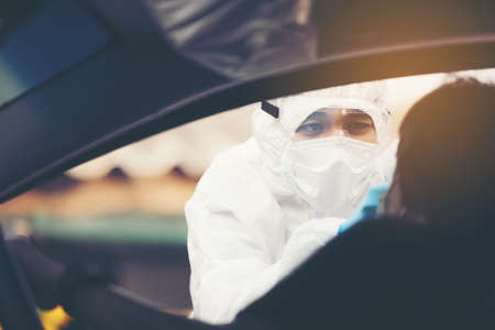 Asian Woman Drive Thru Covid-19 Testing With PPE Medical Staff, COVID testing temp while checking in cars Reklamní fotografie
