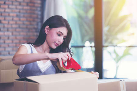 Asian woman packing boxes of parcels in her shopping online business at home.