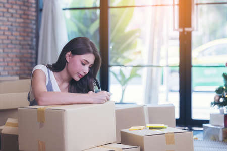 Asian woman packing boxes of parcels in her shopping online business at home. 版權商用圖片 - 167498694