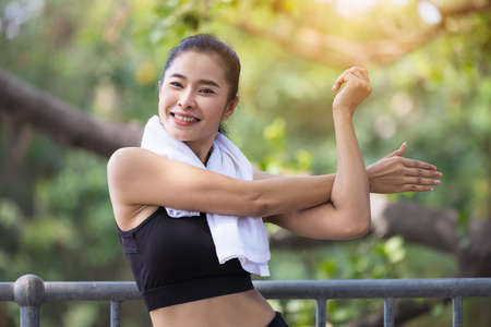 Young woman stretching body after jogging, Happy sporty millennial woman running
