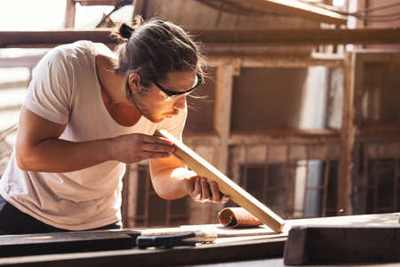 A young male carpenter builder working overall equals a wooden bar with a milling machine in the workshop, in the background wooden 免版税图像