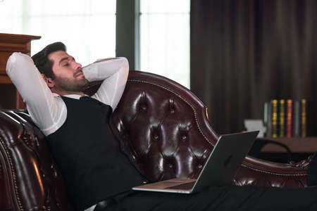 Businessman lying on sofa and Holding Laptop Computer.
