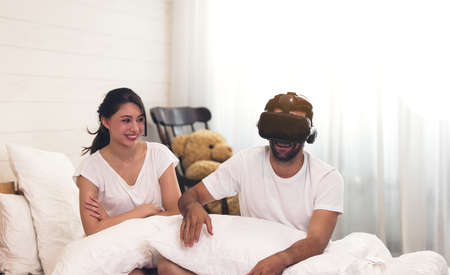 Woman in bed her husband man with short dark hair and 3 day beard using his VR head set gaming video with the 3D glasses, having fun.
