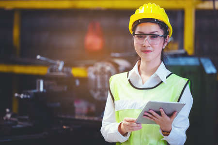 Women industrial plant with a tablet in hand, Engineer looking of working at industrial machinery setup in factory. 免版税图像