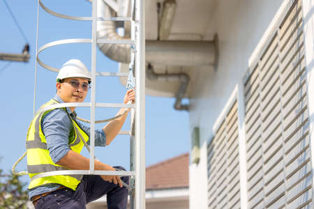 Young man worker or engineer climb ladder.