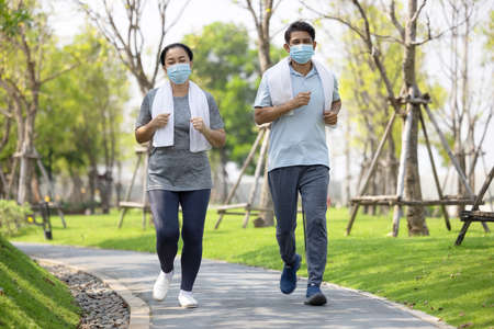 Senior couple wearing face mask and walking trough nature park, summer outdoors workout