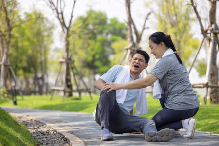 Asian elderly or senior man accident falling down on floor in the park while running exercise have pain knee ache.