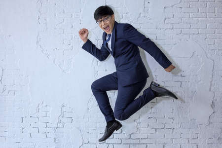 Funny cheerful businessman jumping in air over white wall background
