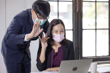 businessman and women wearing face masks while using laptop and greeting someone during video call in the office. conference with work team amid  pandemic.
