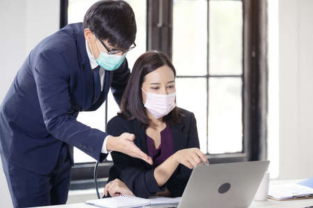 Businessman and Beautiful businesswoman sitting at the desk in the coworking office with face mask 版權商用圖片