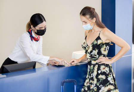 Receptionist hands over a passport to a tourist at te front desk and reception of a hostel 版權商用圖片