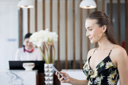 Smiling, confident, modern woman talking and checking social media at mobile phone in the hotel lobby 版權商用圖片 - 167491686