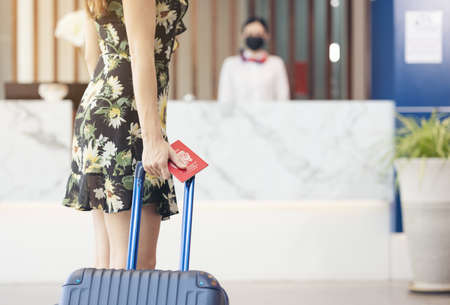 Female traveller with baggage walking to hotel check-in counter. Travelling, holiday and vacation concept