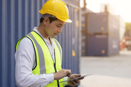 Male engineer, worker inspection checking on container by using tablet.