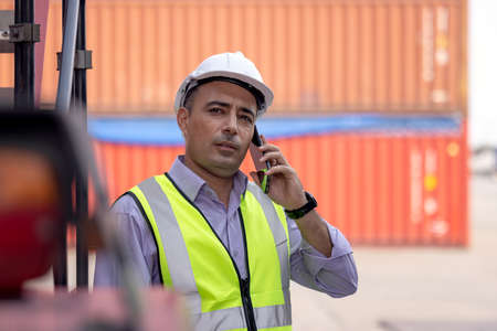Worker helmet standing and talking on mobile phone at logistic cargo containers shipping yard
