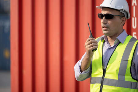 Man engineer using walkie-talkie in shipping yard, Industrial worker is controlling container loading by walkie talkie in import-export business. 版權商用圖片