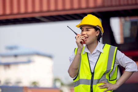 woman factory worker or engineer using walkie talkie and calling someone for preparing a job in containers warehouse storage