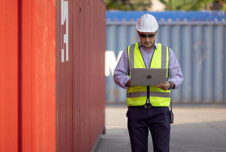 Confident Caucasian man engineer wearing white safety helmet using computer laptop and check for control loading containers box from Cargo freight ship for import and export, transport