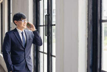 Successful young businessman talking on cellphone near windows 版權商用圖片