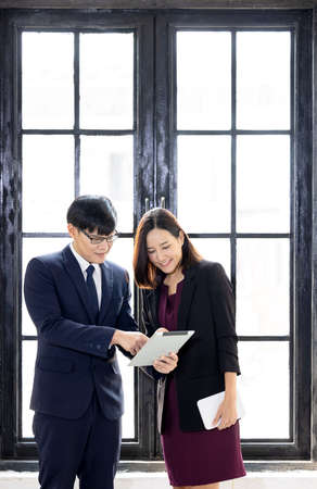 Businessman and businesswoman using a laptop together while standing near window in office