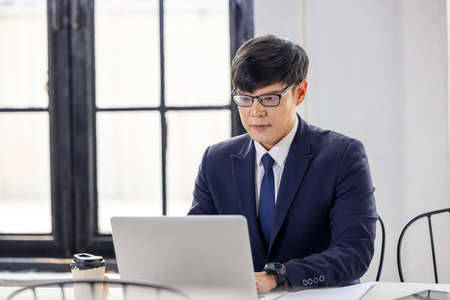 Side view handsome young businessman in eyewear working with computer remotely, sitting at wooden table in kitchen. Pleasant happy man communicating in social network, searching information online.